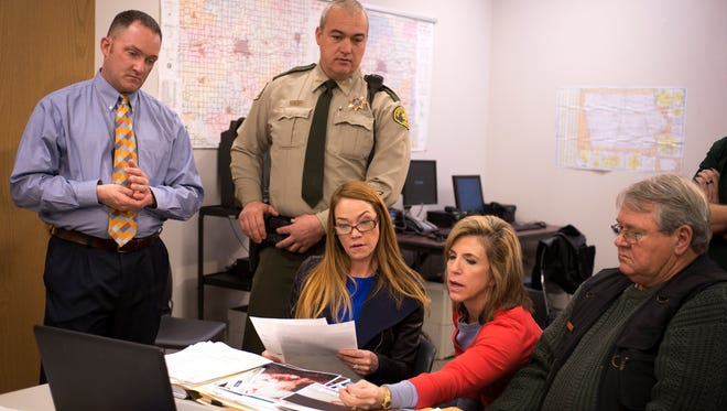 "From left, Division of Criminal Investigation Special Agent Adam DeCamp, Jasper County Sheriff John Halferty, and three members of the ""Cold Justice"" cast — Yolanda McClary, Kelly Siegler and Johnny Bonds — examine crime scene photos in the sheriff's office in Newton."