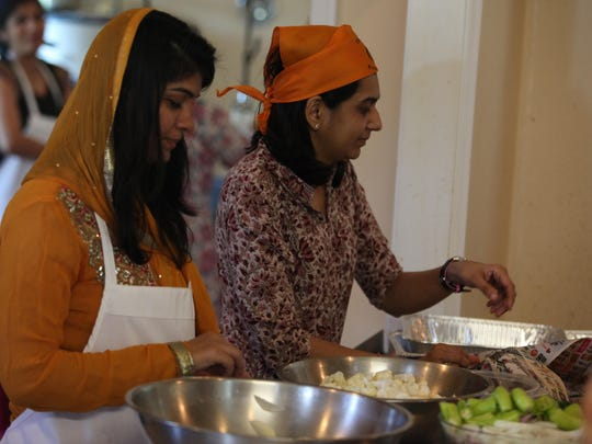 Mukta Bodani (left) and Pinky Bhatt (right) prepare vegetables to be used in the Sikh Center of Delaware's weekly communal meal.