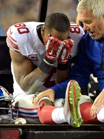Giants WRVictor Cruz is carted off the field after