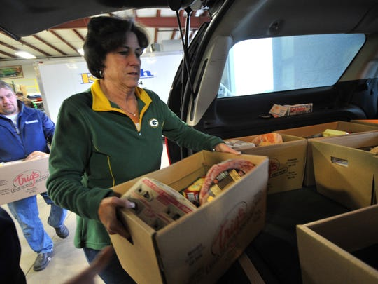 Volunteers Deb Pagel, right, and Butch Raasch, both of Weston, help load food baskets Sunday at K-tech Kleening in Weston.