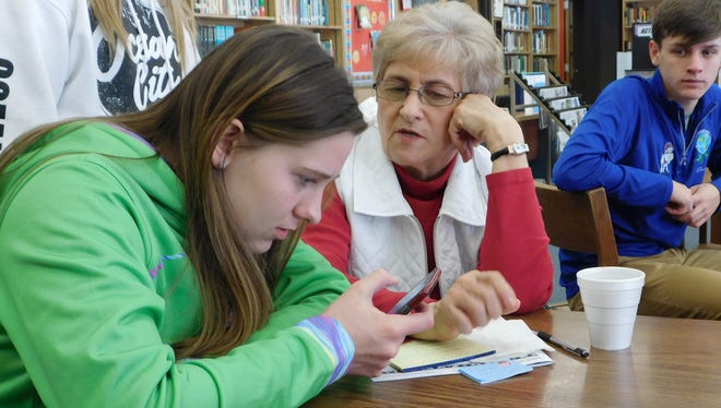 Fremont Ross senior Logan Lamalie, left, works on some apps on an iPhone for Mary Lou Baker, right, during 'Coffee with Giants' on Feb. 14.