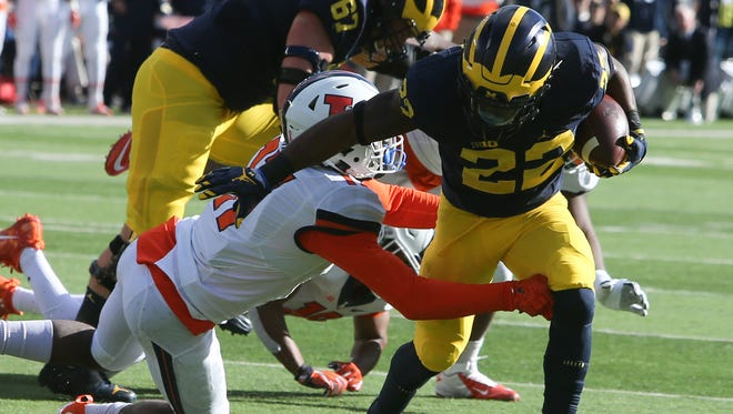 Michigan's Karan Higdon runs by Illinois' Stanley Green during first quarter Saturday at Michigan Stadium.