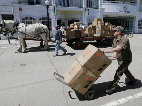 In a photo from Wednesday, May 6, 2015 in Mackinac Island Mich., United Parcel Service driver Dan Minta delivers packages on the island using a horse drawn cart.