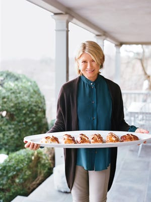 Timeless Traditions: Martha holds a platter with individual portions of salmon coulibiac, a take on a classic Russian dish.