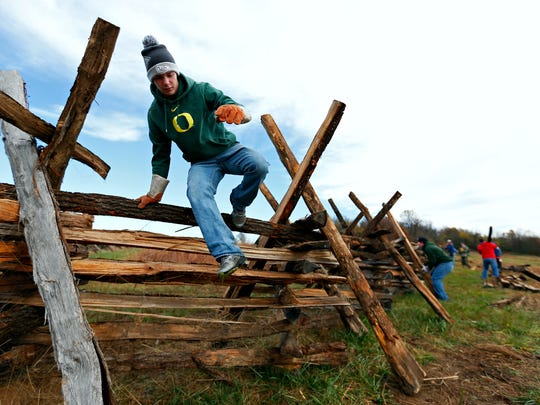 Logan Swearengin jumps over the split rail fence he and his friends and family are building as a community service project for him and his triplet brothers Ethan and Austin to earn their Eagle Scout badge. The fence is being built at the historical fence line of the Ray property at Wilson's Creek National Battlefield in Republic, Mo. on Nov. 7, 2015.