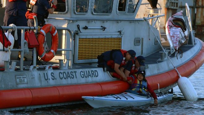 "U.S. Coast Guardmen detain a ""kayactivist"" June 15, 2015, as protesters try to blockade Shell Oil's Polar Pioneer drilling rig from leaving Seattle for the Arctic."