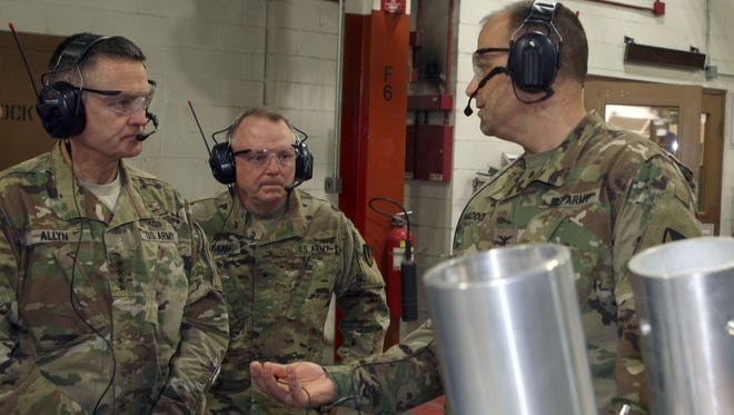Letterkenny Army Depot Commander Col. Deacon Maddox on Thursday discusses the AMG upper antenna positioner with Gen. Dan Allyn, Vice Chief of Staff of the US Army and AMCOM's Commanding General Brig. Gen. Douglas Gabram. In the foreground is an example of a one-piece construction design milled on the depot's 9-Axis Mazak machine.