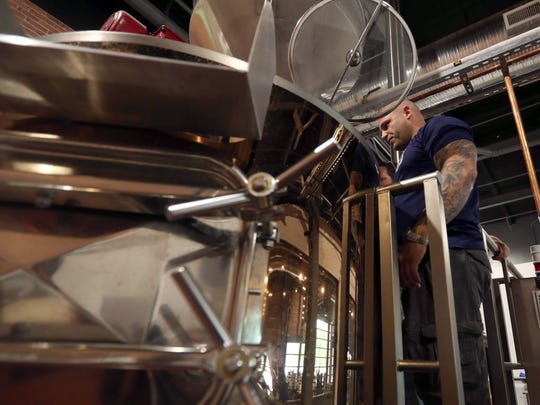 """Brandon Kruithof, President of the Peekskill Police Benevolent Association, looks into the tank where beer is brewing at River Outpost Brewery in Peekskill May 22, 2018. The brewery is partnering with the police department in creating a beer called """"PeaceSkill"""" that will be sold as a fundraiser for the police departments gun buyback program."""