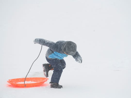 PJ Britt, 4, hops up from his sled for another trip up the hill at the Henderson Municipal Golf Course where he and his mom and dad, Lacey and Paul Britt of Henderson, took advantage of the snow day Friday.
