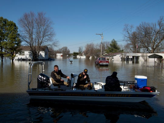 Henderson County Sheriff Keith Berry, left, and Sgt. Carroll Morrow take off from Cagey's General Store in Beals, Ky., to drop off a local resident whose home is surrounded by water Monday afternoon. The Ohio River continues to rise and is expected to crest Wednesday.