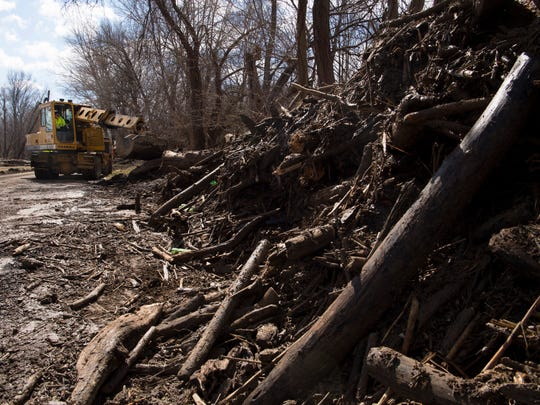 Harold Lee Stuckey with the Vanderburgh County Highway Department uses his Gradall to remove flood debris from Old Henderson Road as clean-up began last week.