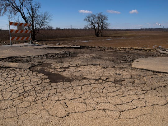 The top layer of asphalt washed-out into the farm field at the intersection of Duesner and Seminary roads leaving the cracked and broken road beneath when floodwaters receded last week.