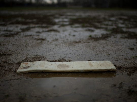 A pitching rubber at the Burdette Park baseball fields is surrounded by standing water from spring flooding Tuesday afternoon. The fields are unplayable until the rain lets up.