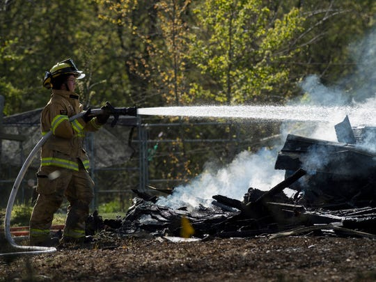 Andria Spall with the Lynnville Fire Department puts water on the remains of a house that burned to the ground on Hwy 61 south of Lynnville, Ind., Monday afternoon. It was earlier thought a dog and cat had perished in the fire, but the dog was later found in a pen in the backyard.