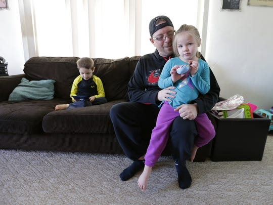 Rob Brooks holds Charlie, 3, on the couch at their home Wednesday, March 28, 2018, in Manitowoc.