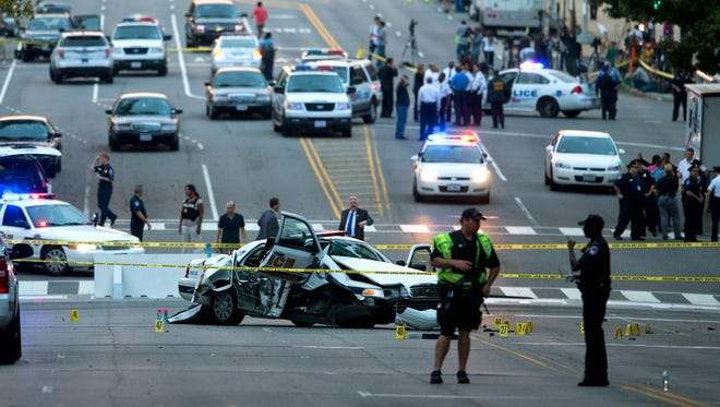 A damaged Capitol Hill police car is surrounded by crime scene tape on Constitution Avenue near the U.S. Capitol after a car chase and shooting Thursday.