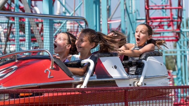 Brook Doughtery, left,  Hannah Viera, Bella Zabaleta and Ava Valadao take the last turn on the Dynamic Bobsled at the Tulare County Fair on Wednesday, September 13, 2017.