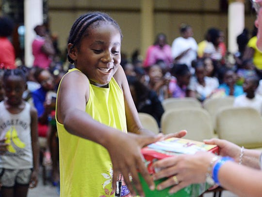 Eden Beazer, 9, receives an Operation Christmas Child box at Restoration Church in Antigua November 7, 2017. Beazer was displaced from her home in Barbuda, a Caribbean island 25 miles away that is currently uninhabitable after Hurricane Irma.