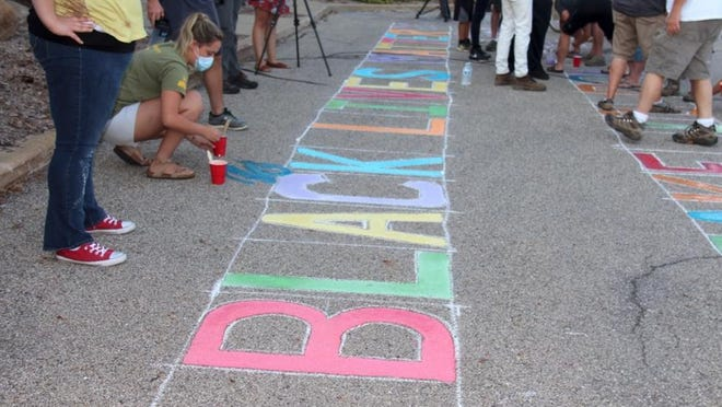 """A Black Lives Matter protest took place in Allendale on Sunday, Aug. 23. Protesters painted the phrase """"Black Lives Matter"""" in front of the township offices in response to the township board's decision to let a controversial Civil War statue remain."""