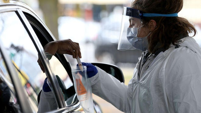 Registered nurse Anna Reinhart collects a self-administered COVID-19 test at a drive-through testing site at Rush University Medical Center in Chicago on  Oct. 20, 2020.