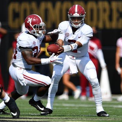 Alabama running back Damien Harris (34) is handed