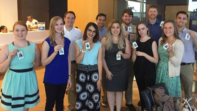 Fellows in the 2017 Pulliam program at The Arizona Republic show off their press badges.
