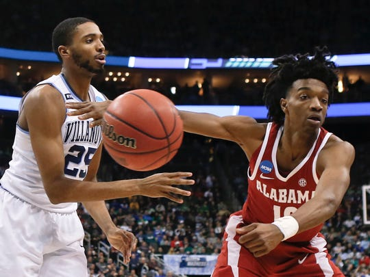 Villanova's Mikal Bridges (25) passes away from Alabama's Herbert Jones during the second half of a second-round game in the NCAA men's college basketball tournament, Saturday, March 17, 2018, in Pittsburgh. Alabama won 81-58. (AP Photo/Keith Srakocic)
