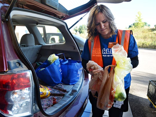 Lori Arnold loads groceries into a vehicle at the North College King Soopers Wednesday in Fort Collins. King Soopers has started offering online grocery ordering that can be picked up curbside.
