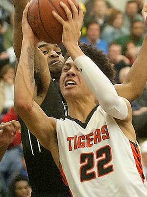 Trinity forward David Burton tries to block the shot of the driving Fern Creek guard Chance Moore on his way to the basket.18 December 2016