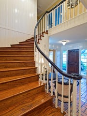 A charming, curved, wood stairway sets the tone for