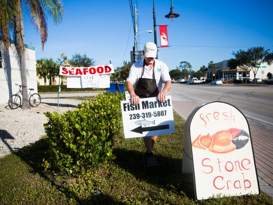 Jim Weeks adjusts a sign outside of the new fish market