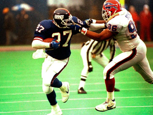 Running back Rodney Hampton (27) of the New York Giants is spun around as he is facemasked by Leon Seals of the Buffalo Bills.