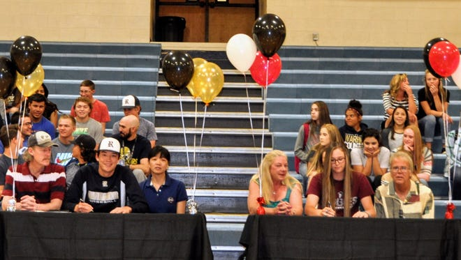 Ruidoso High School students Alex Bates and Lia Mosher sign letters of intent Monday at Ruidoso High School. Seated, from left; Steve Bates, Alex Bates, Ayako Bates, Leslie Carroll, Lia Mosher and Brian Mosher.