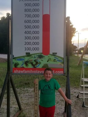 Maddux Shaw holds a sample engraved fence picket while standing in front of the fundraising sign at the site of the future playground on July 10.