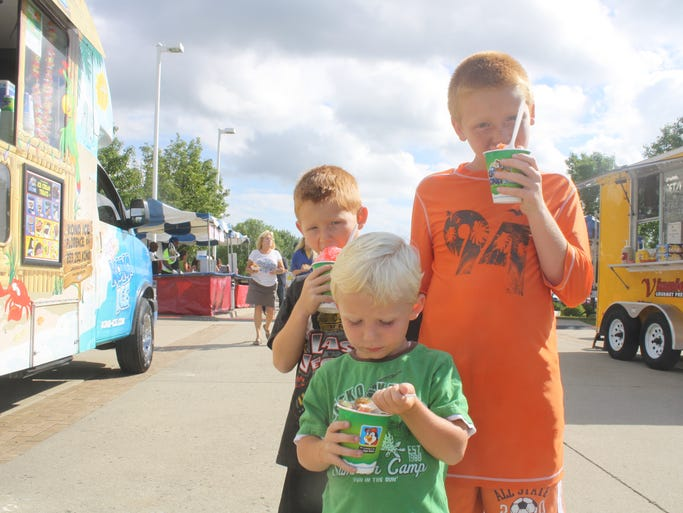 Dane Williams (front), 3, and Reid Williams, 6, and Chase Williams, 9, of Independence enjoy some Kona Ice at the Florence Independence Day celebration on Thursday.