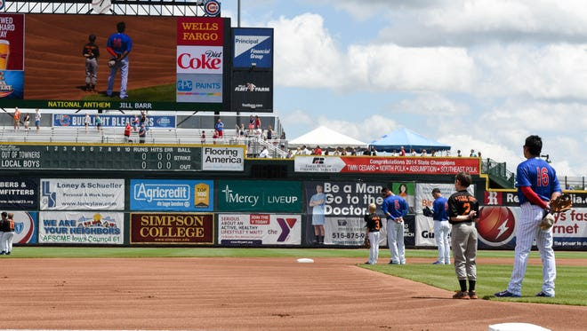 Iowa Cub players stand with the Pleasantville Black Baseball team during the National Anthem on Monday, May 25, 2015, during the baseball game held at Principal Park.