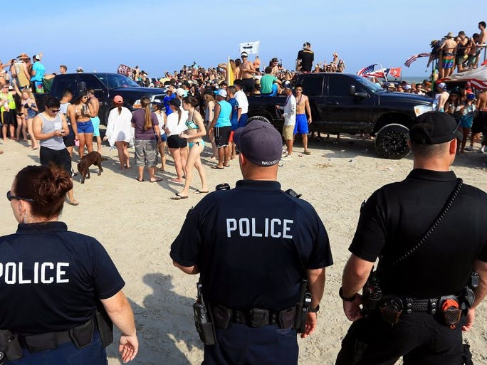 Police officers from Port Aransas Police Department and other area agencies watch for illegal activity as beach goers dance and drink during spring break Tuesday, March 15, 2016, in Port Aransas.