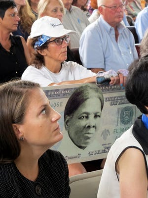 In this Monday, Aug. 31, 2015, file photo, a woman holds a sign supporting Harriet Tubman for the $20 bill during a town hall meeting at the Women's Rights National Historical Park in Seneca Falls, N.Y.