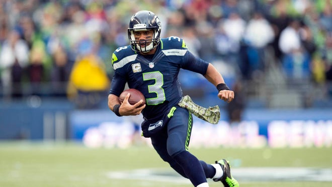 Seahawks quarterback Russell Wilson (3) carries the ball against the New York Giants during the first half at CenturyLink Field.