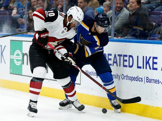 Arizona Coyotes' Anthony Duclair (10) and St. Louis Blues' Jaden Schwartz chase the puck along the boards during the first period of an NHL hockey game Thursday, Nov. 9, 2017, in St. Louis. (AP Photo/Jeff Roberson)