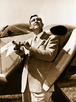 In this 1947, file photo, Kenneth Arnold, holds a movie camera in front of his CallAir, after he reported seeing nine alleged UFOs near Mount Rainier, Wash. Arnold had no idea he would change the world when he told reporters in Pendleton he saw nine strange objects flying along the Cascades. But 70 years ago June 25, that's what he did.