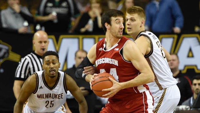 Wisconsin Badgers forward Frank Kaminsky (44) gets pressure from UW-Milwaukee Panthers guard Steve McWhorter (25) and forward J.J. Panoske (23) in the first half.