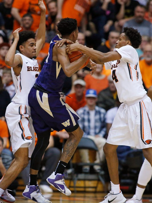Washington's Dejounte Murray, center, is guarded by Oregon State's Stephen Thompson Jr., left, and Derrick Bruce during the first half of an NCAA college basketball game in Corvallis, Ore., Wednesday, Feb. 24, 2016.  (AP Photo/Timothy J. Gonzalez)
