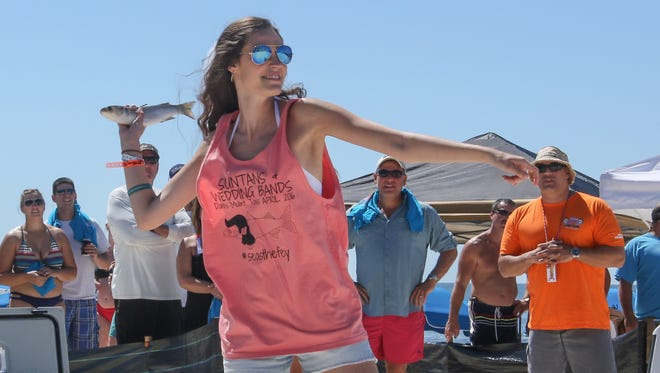 Danielle de Mond of Baton Rouge, La., throws a mullet Saturday during the 2016 Flora-Bama Interstate Mullet Toss.