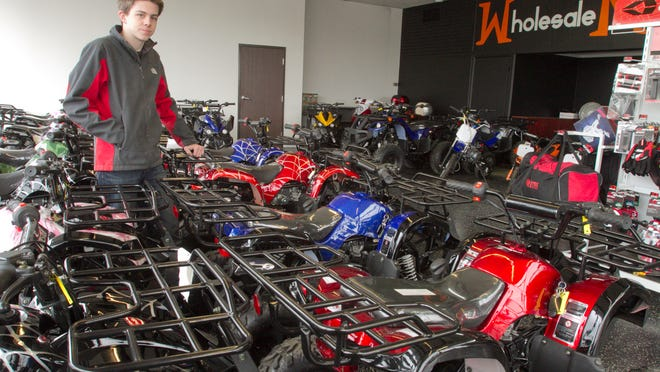Carter Valente, son of Wholesale Motorsports owner Darren Valente, stands amid the all-terrain vehicles in the showroom of the Brighton store.