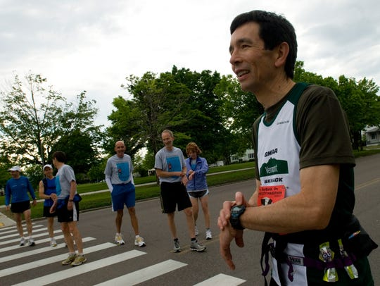 Pascal Cheng of Burlington sets his watch before running the Vermont City Marathon loop through Burlington with a group of friends on May 31, 2009.