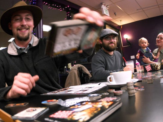 Chase Carlton, at left, grabs a deck of cards to deal to his friends before they play a zombie apocalypse game on Dec. 3 at The Haunted Game Cafe in Fort Collins. Carlton said he has been to the new shop twice and enjoys it because he is able to play games before committing to spending money on them.