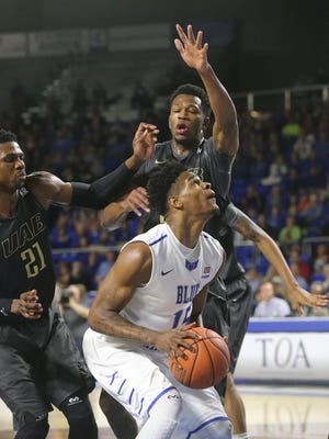 MTSU's Aldonis Foote (15) goes up for a shot as he is guarded by UAB's Tosin Mehinti (21) and William Lee (34) on Sunday at MTSU.