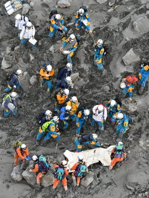 Rescuers struggle in the ash-covered muddy slope as they carry down the body of a newly-found victim from the summit of Mount Ontake on Oct. 4, 2014. Search operations were called off Oct. 5 due to the approach ofTyphoon Phanfone.