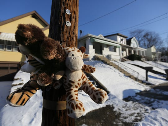 A makeshift memorial sits outside the house where Georta Mack was shot and killed by his father.